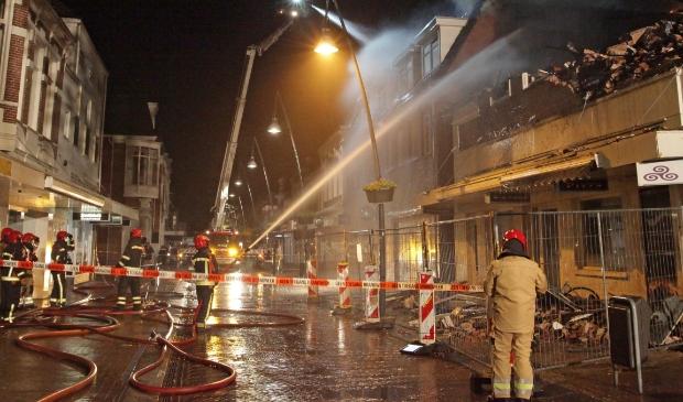 <p>Brandweermannen bestrijden de brand in de Kerkstraat in Veendam. Foto: Bert Woltjes.&nbsp;</p>