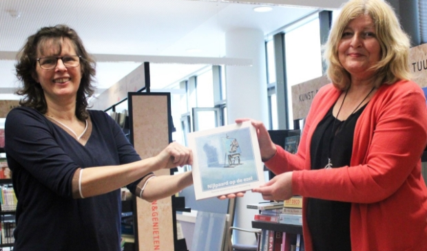 Remda Spoelstra overhandigt het boek aan bibliotheekdirecteur Janneke Klok.