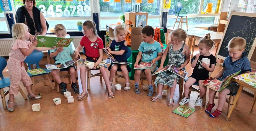 Kinderen van IKC de Bosvlinder lezen in het kookboek met daarin ook hun recept (foto Gemeente Midden-Drenthe).  © De Veldenkrant