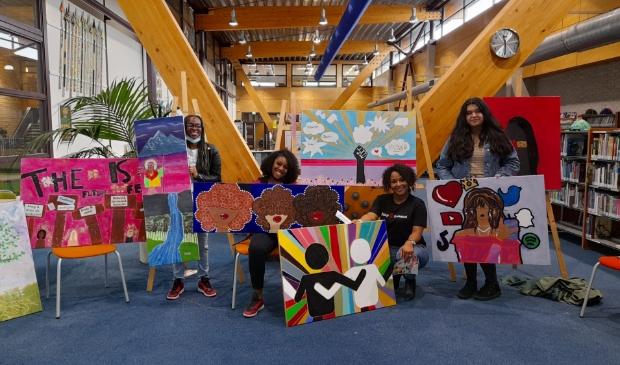 Kunstenares Ailyne Stein (tweede van rechts) en een aantal leerlingen tonen trots de gemaakte kunstwerken. (Foto: Almere DEZE WEEK)
