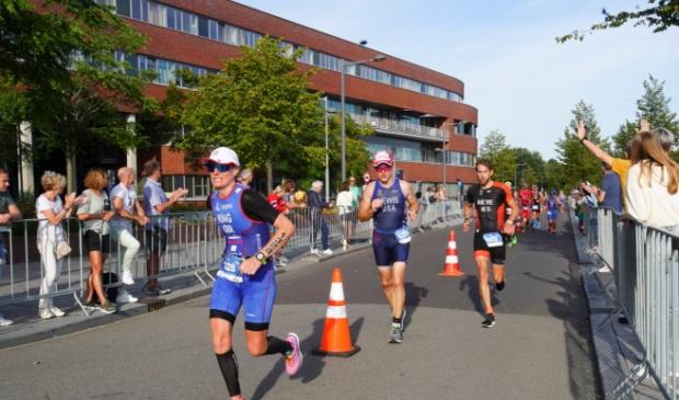 De atleten passeren tijdens het looponderdeel het ziekenhuis. (Foto: Fred Rotgans)