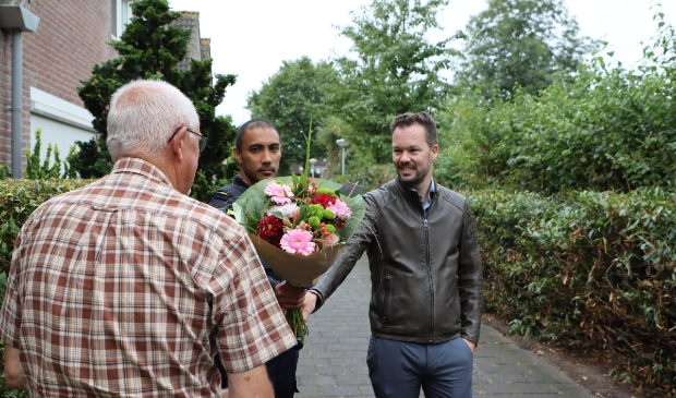 De bewoners, die niet herkenbaar op de foto wil, kreeg een bloemetje als dank. (Foto: Studio Rotgans/RInus Lettinck)