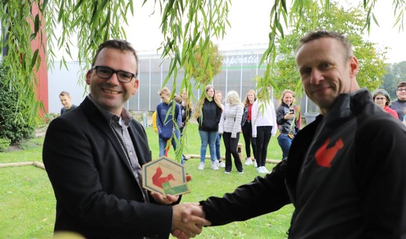 Schoolmanager Michel van Loon van Curio - Steenspil neemt de plaquette in ontvangst  uit handen van Robert Deliën van het Natuurpodium.