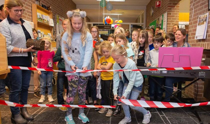 Twee linten werden er  doorgeknipt en daarna namen de mini Krekels en het Krekelkoor vol enthousiasme het aanwezige publiek mee op hun muzikale reis waarmee de Kinderboekenweek in de bibliotheek van Huijbergen officieel was geopend.