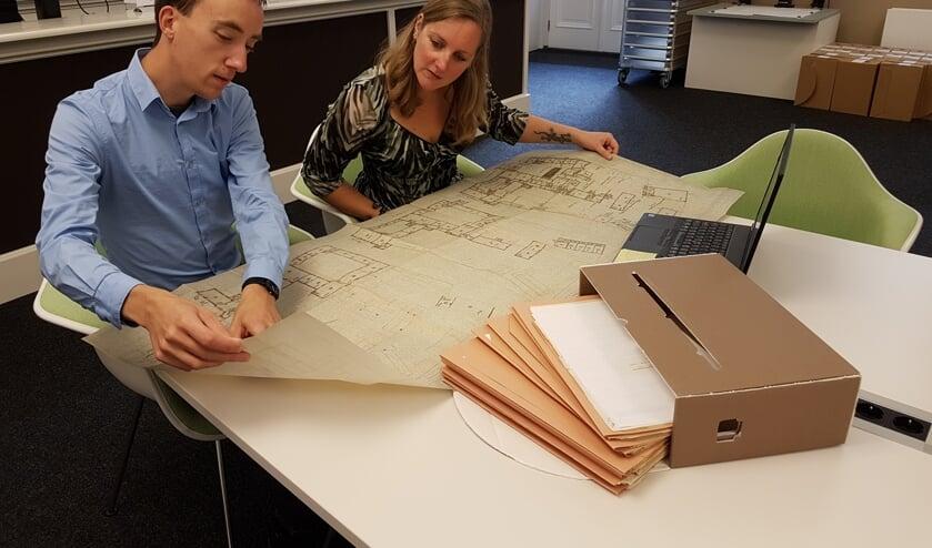 Onderzoeker Bart van Eekelen toont medewerker Dienstverlening Saskia van Bavel een plattegrond van het Markiezenhof die het West-Brabants Archief voor hem heeft gedigitaliseerd.