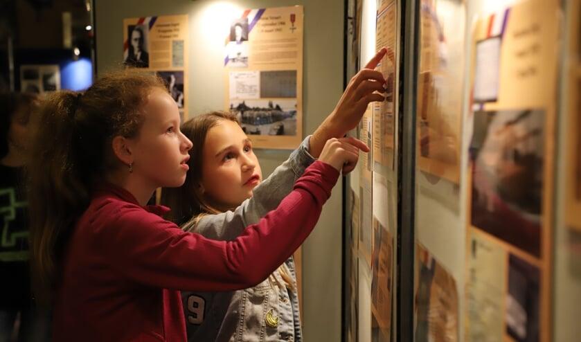 Schoolkinderen bekijken aandachtig de tentoonstelling over de Tweede Wereldoorlog die is opgezet bij heemkundekring Halchterth.