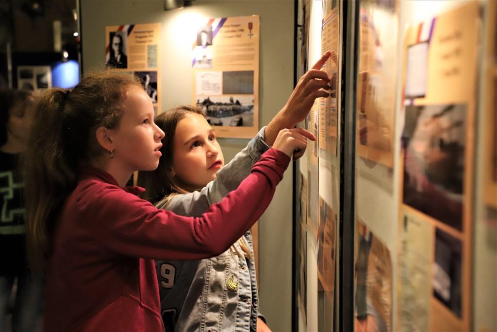 Schoolkinderen bekijken aandachtig de tentoonstelling over de Tweede Wereldoorlog die is opgezet bij heemkundekring Halchterth in Hof van Ram.   © Minerve Pers