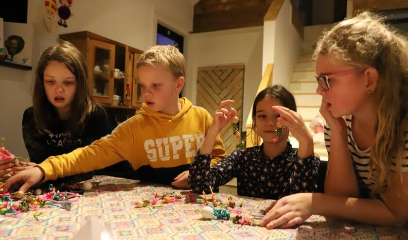 Kinderen van buitenschoolse opvang Zo op 't Groene Hart knutselen gelukspoppetjes bij dagbesteding 'op 't Dorp' voor de kerstmarkt.