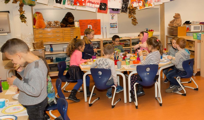Kinderen genieten op de basisschool van een gezond Koningsontbijt.