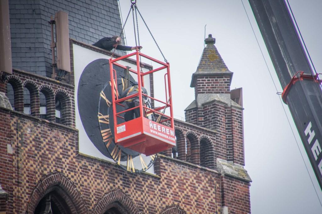 Klokkenmaker Ralph van Veghel loodst het loodzware uurwerk naar beneden.  © Minerve Pers