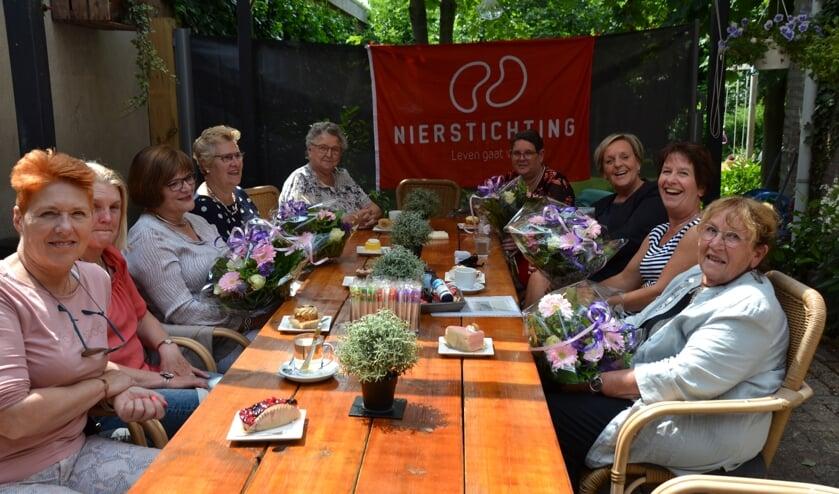 Jubilarissen met bloemen tussen anderen die zich al jarenlang inzetten voor de Nierstichting.