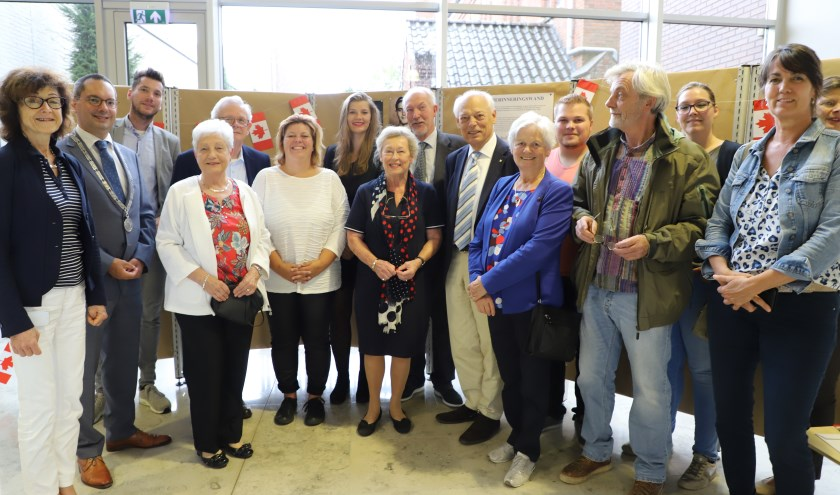 Familie van de 75 jaar geleden gefusilleerde Sjef Adriaansen en gemeentebestuurders bij de herinneringswand.