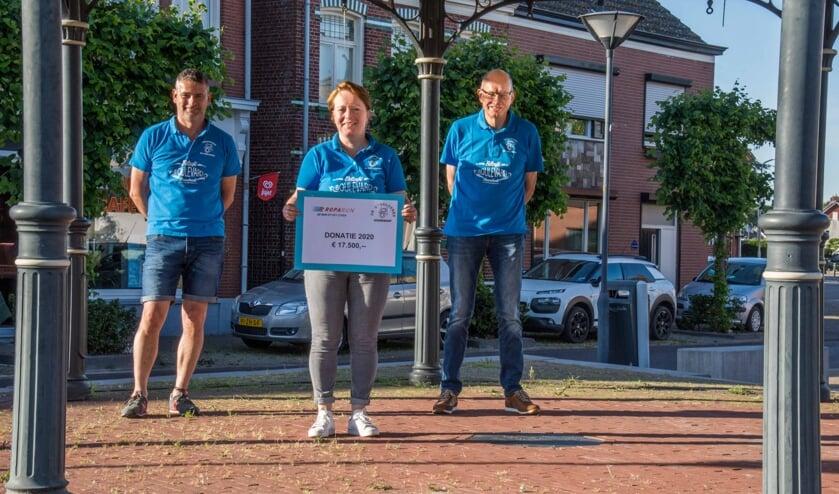 Teamcoördinator Elly-May van Ginneken presenteert de cheque voor de Stichting Roparun, met teamleden Marcello Hoezen en Jules Theuns.