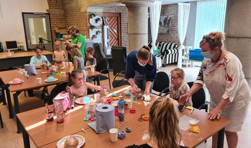 <p>Jonge mantelzorgers vermaken zich met taartjes versieren.</p>