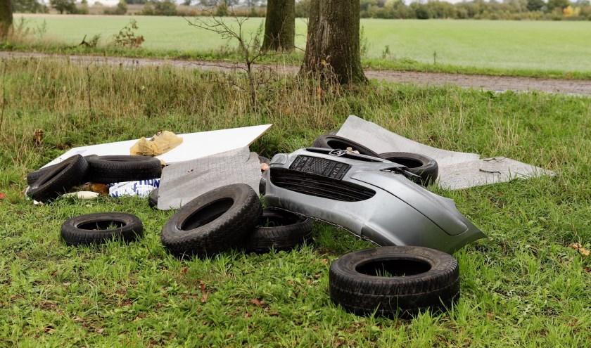 Auto-onderdelen en banden gedumpt in een weiland in Beers.
