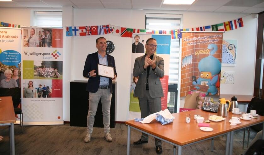 Roland van der Heijden (links) van Sociom ontving uit handen van Lex Staal van Sociaal Werk Nederland het Kwaliteitslabel Sociaal Werk.