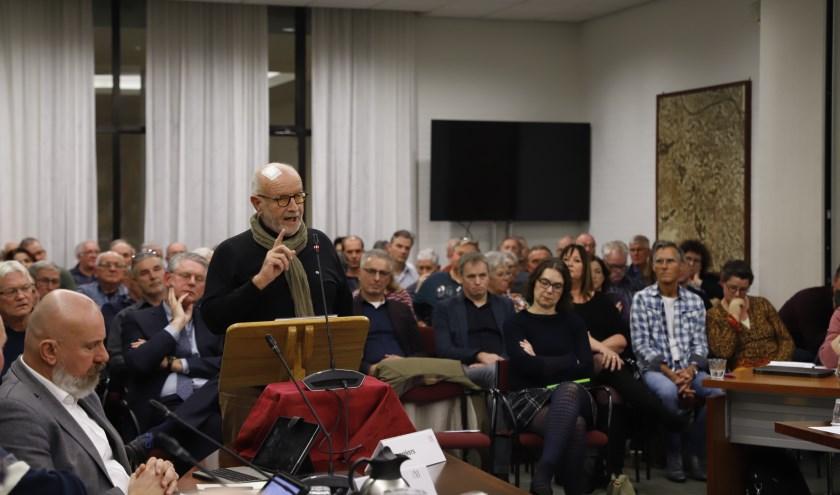 Ad Berends licht de 1.800 zienswijzen van de werkgroep toe tijdens de drukbezochte gemeenteraadsvergadering in Mill.