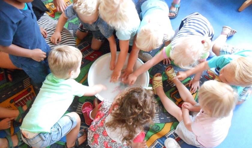 De peutergroep wast de kleertjes van pop Puk bij Kinderopvang De Dag Door in Boxmeer.