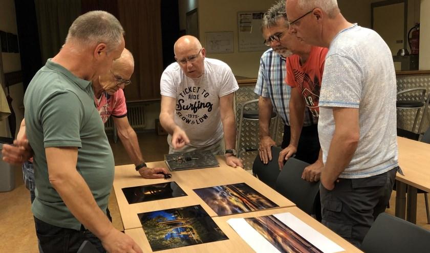 De leden kijken naar de afdruk die een clubgenoot meegebracht heeft. (foto: Jos Gröniger)