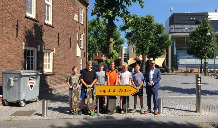 De jongens na hun aankomst in Uden, samen met wethouder Gijs van Heeswijk.