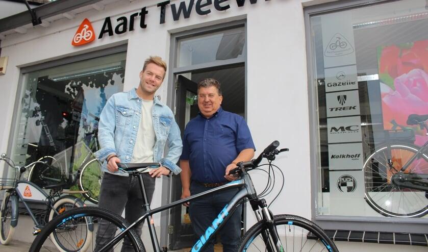 Luc Vaessen ontvangt van Aart van Egdom (rechts) een mountainbike van Giant.