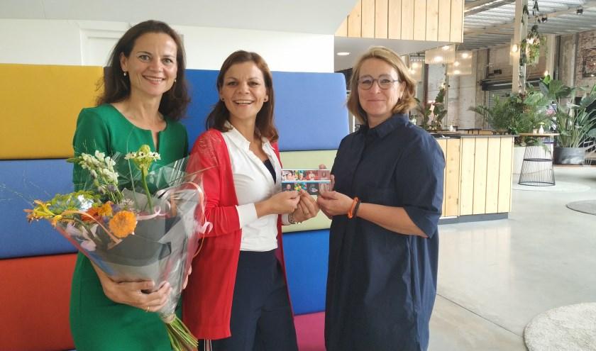 Diana van Huijgevoort van De Blauwe Kei overhandigt de prijs aan mevrouw Greenall en haar zus.