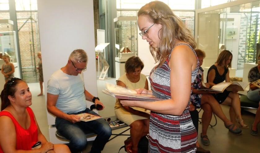 Annabel Spanjersberg, lid educatiegroep van het Graafs Museum, deelt het boek 'Wat is het je waard' uit.