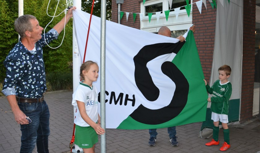 Erelid Bert van den Broek onthult de nieuwe vlag samen met de pupillen Lynn en Morris.