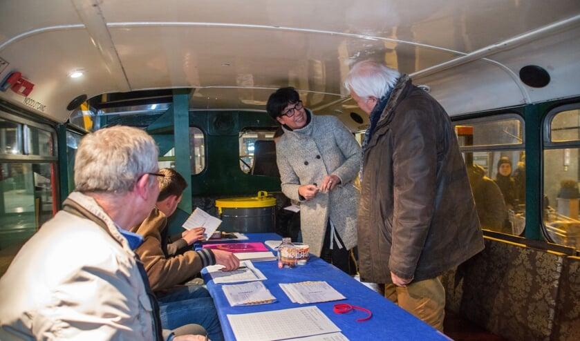 <p>Nol van Hest (R) staat een bezoeker te woord in de mobiele stembus. Iets wat tijdens de komende verkiezingen niet op deze manier mag.</p>