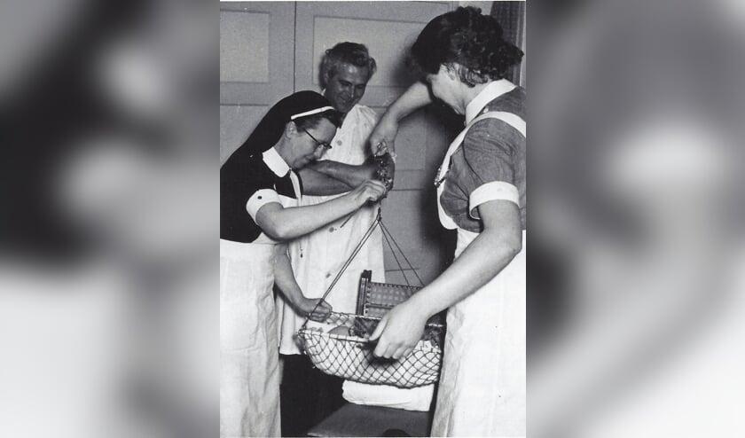 Zuster Van Uffelen (links), docente van het Kraamzorgcentrum in Veghel met de arts Van Kuppevelt (midden) en een kraamverzorgster in 1956.