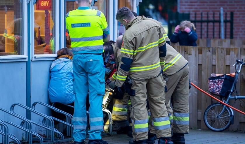 Brandweerlieden bevrijden kindje uit fietsenrek bij De Polderhof. (Foto: Gabor Heeres, Foto Mallo)