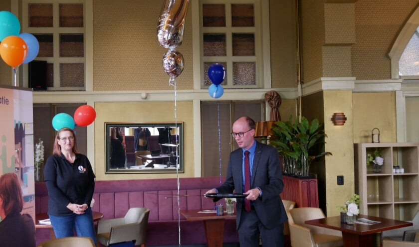 Wethouder Joost Hendriks van gemeente Cuijk opent symbolisch het informatiepunt in de Cuijkse bibliotheek.
