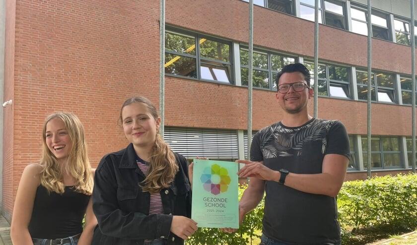 <p>Leerlingen Quinty en Lotte, en docent/co&ouml;rdinator Jos tonen de plaquette Gezonde School. Patricia maakte de foto.</p>