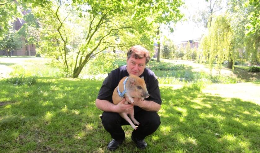 <p>Kapelaan Willem Renders in de pastorietuin met &eacute;&eacute;n van zijn huisdieren: een varkentje. </p>