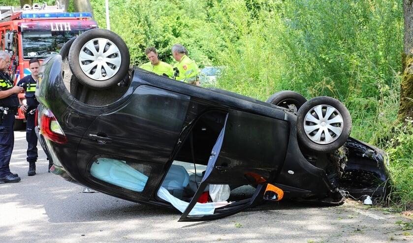 Auto botst in Lithoijen tegen boom en slaat over de kop. (Foto: Charles Mallo, Foto Mallo)