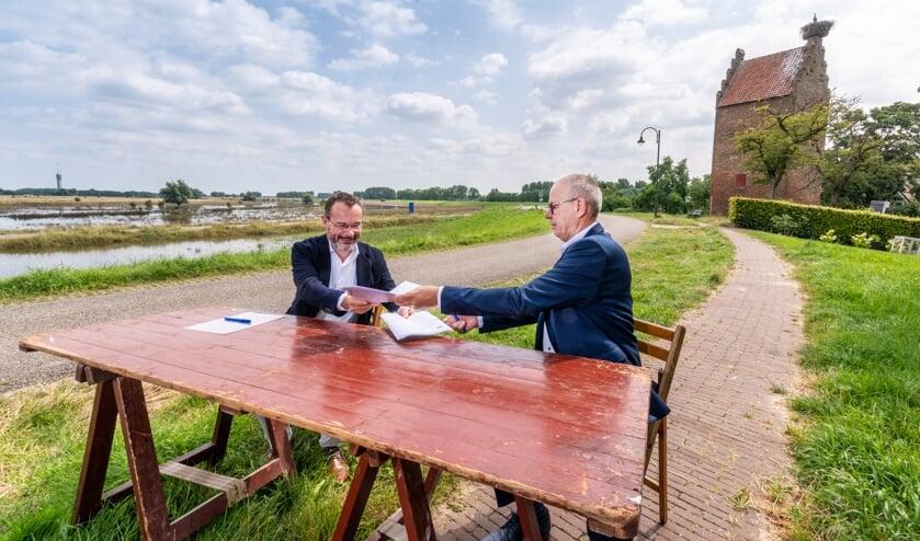 <p>Mario Jacobs en Maar van Oord zetten hun handtekening.</p>