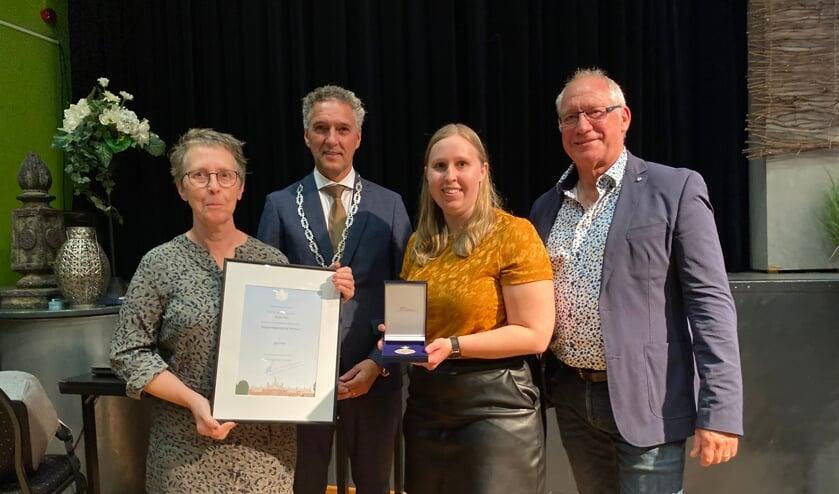 <p>Het trotse bestuur toont de Erepenning en oorkonde. Vanaf links Ilze Elemans, burgemeester Hans Teunissen, Floortje Elemans en Willem Elders.</p>