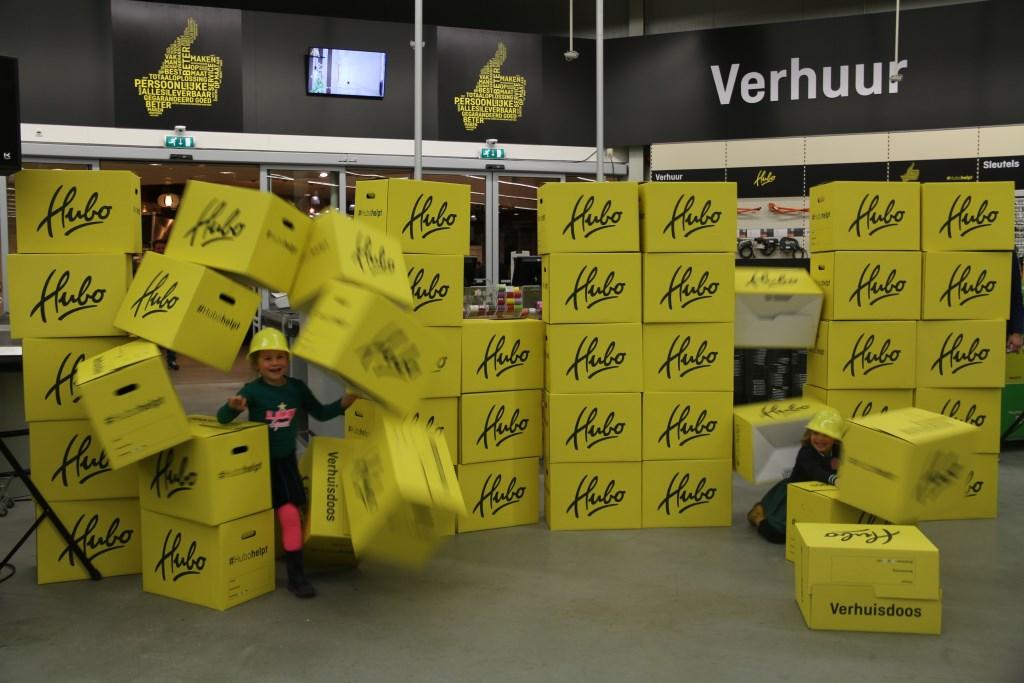 Lieke en Milou, de dochters van Patrick Zwanenburg verrichten de officiële opening van de nieuwe formule door dwars door een muur Hubo-dozen te springen  © Graficelly B.V.