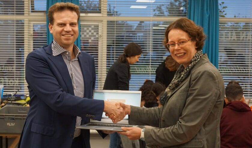 Rotary-voorzitter Arjan de Knikker en OKÉ-klas coördinator Agnes van der Kraan met één van de nieuwe Chrombooks.