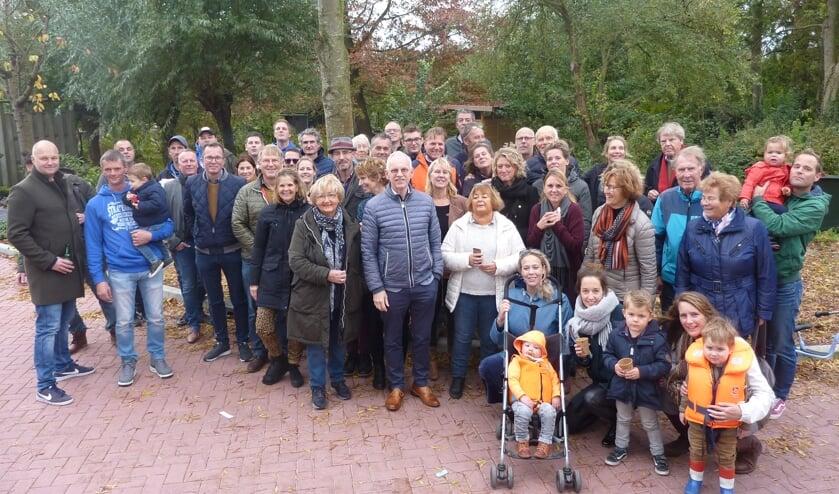 Buurtbewoners, werkmannen en gemeente op groepsfoto.