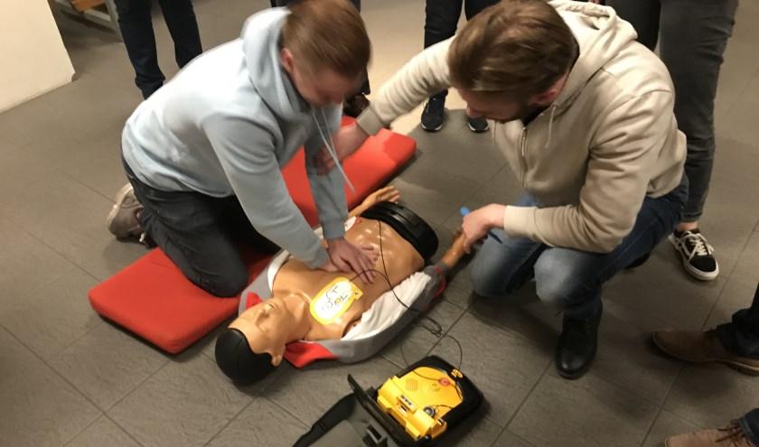 Twee deelnemers oefenen met de AED