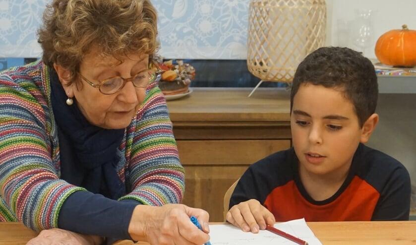 <p>Vrijwilliger Charmian helpt met het huiswerk in de OK&Eacute;-klas van Bureau Bousa.</p>
