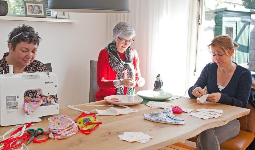 Marjolein Kranenburg (links), Inge Wisselink en Wilma Neven druk aan het werk aan de mondkapjes.