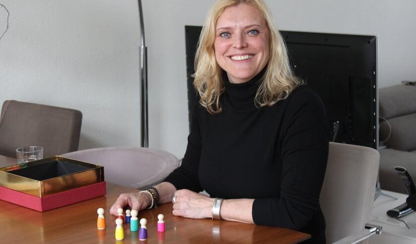 <p>Helma Horsmans en haar houten poppetjes. Elk popje staat voor een van de familieleden.</p>
