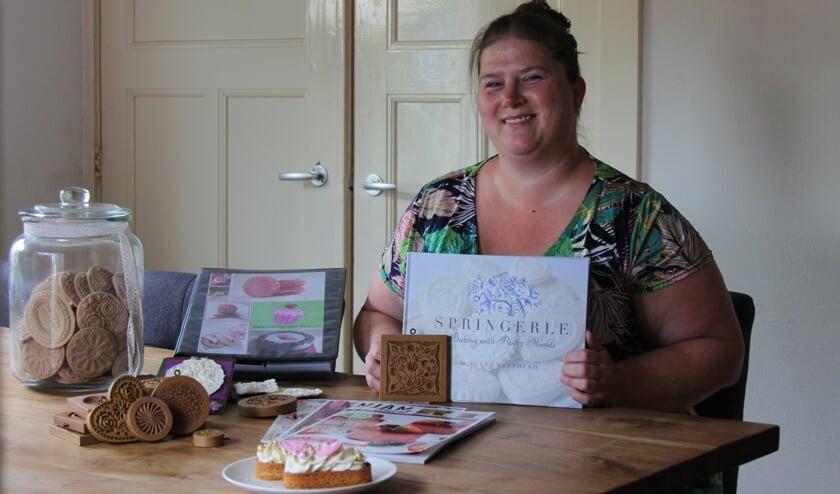 <p>Marlies, met in haar handen het Amerikaanse boek dat vol van haar creaties staat.</p>