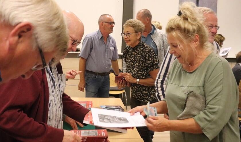 <p>In de pauze van de presentatie, toont de familie Kooistra zich reuze nieuwsgierig naar het boek. In het midden schrijver Ruud Kooistra.</p>