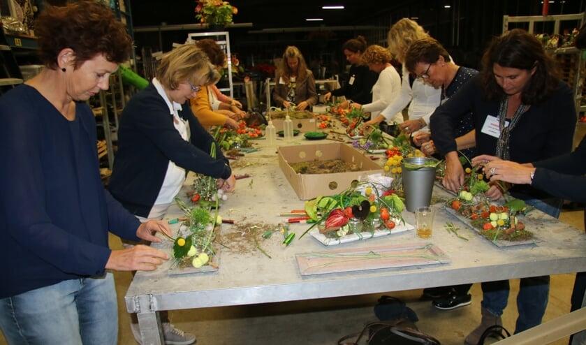 De leden van NOOVA maken een prachtige herfstcreatie met anthuriums uit de kwekerij.