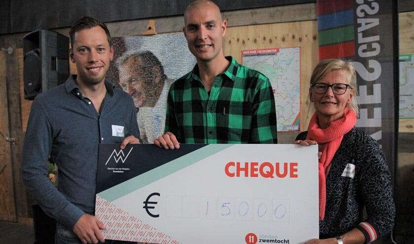 Marja en Gijs van der Helm overhandigden een cheque met 15.000 euro aan Maarten van der Weijden, die dit jaar als eerste mens op aarde de Friese Elfstedentocht helemaal zwom.
