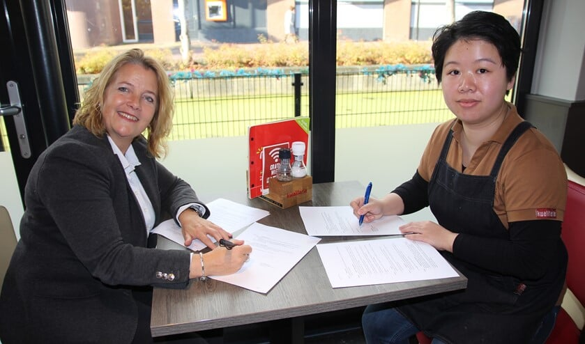 De wethouder en de eigenares van Kwalitaria ondertekenen de overeenkomst.