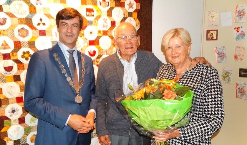 Hans en Riet poseren met de burgemeester voor een van Riets zelf gemaakte wandkleden. (Foto: AvdH)